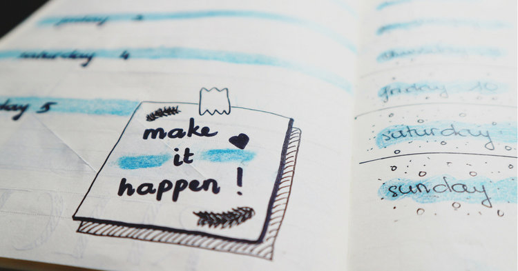"Close up of notebook with note reading ""make it happen"""